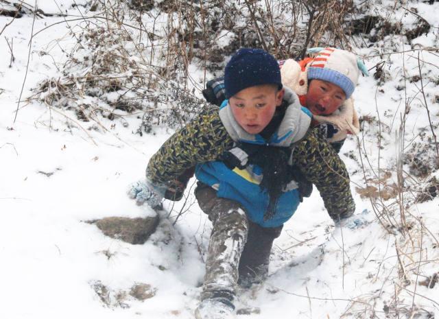 男孩冒雪背弟弟搬新家 走50分钟山路